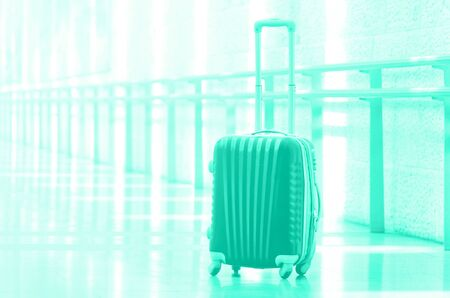 Packed travel suitcase, airport. Summer holiday and vacation concept. Trendy green and turquoise color. Traveler baggage, brown luggage in empty hall interior. Copy space.