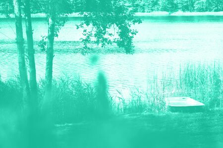 River landscape, tree, boat. Pure nature in mint color background. Summer concept. Biscay Green color of the year 2020