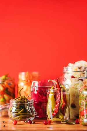 Assortment of various fermented and marinated food over wooden background, copy space. Fermented vegetables, sauerkraut, pepper, garlic, beetroot, korean carrot, cucumber kimchi in glass jars 스톡 콘텐츠
