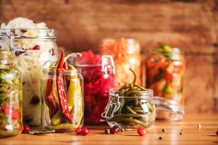 Probiotics food background. Korean carrot, kimchi, beetroot, sauerkraut, pickled cucumbers in glass jars. Winter fermented and canning food concept. Banner with copy space. 免版税图像