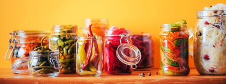 Assortment of various fermented and marinated food over wooden background, copy space. Fermented vegetables, sauerkraut, pepper, garlic, beetroot, korean carrot, cucumber kimchi in glass jars