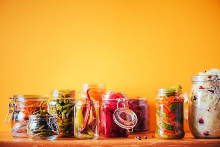 Probiotics food background. Korean carrot, kimchi, beetroot, sauerkraut, pickled cucumbers in glass jars. Winter fermented and canning food concept. Banner with copy space. 写真素材
