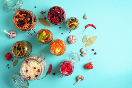 Assortment of various fermented and marinated food over blue background, copy space. Top view. Banner. Fermented vegetables, sauerkraut, pepper, garlic, beetroot, korean carrot, cucumber kimchi in glass jars.