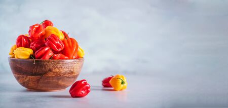 Yellow and red scotch bonnet chili peppers in wooden bowl over grey background. Copy space Stock Photo