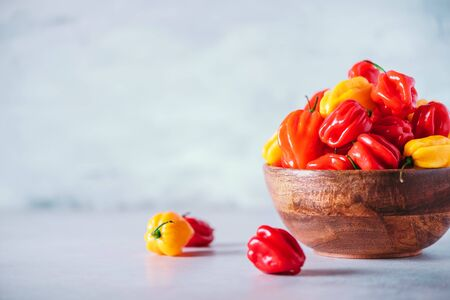 Colorful scotch bonnet chili peppers in wooden bowl over grey background. Copy space