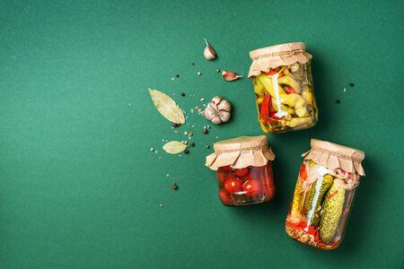 ? komkommer, pompoen en tomaten beitsen en inblikken in glazen potten. Ingrediënten voor het bewaren van groenten. Gezond gefermenteerd voedselconcept. Bovenaanzicht. Ruimte kopiëren Stockfoto