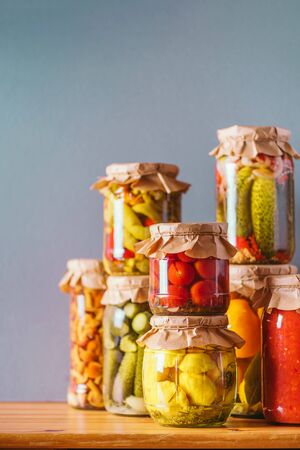Preserved and fermented food in glass jars. Fermented food. Autumn canning. ?ucumber, squash and tomatoes pickling and canning into glass jars