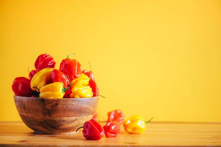 Colorful scotch bonnet chili peppers in wooden bowl over orange background. Copy space
