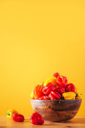 Yellow and red scotch bonnet chili peppers in wooden bowl over orange background. Copy space Stock Photo
