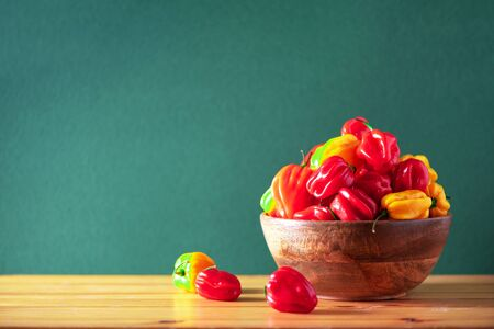 Colorful scotch bonnet chili peppers in wooden bowl over green background. Copy space Stock fotó