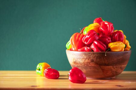 Yellow and red scotch bonnet chili peppers in wooden bowl over green background. Copy space Stock Photo