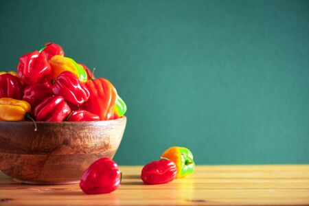 Colorful scotch bonnet chili peppers in wooden bowl over green background. Copy space Stock Photo