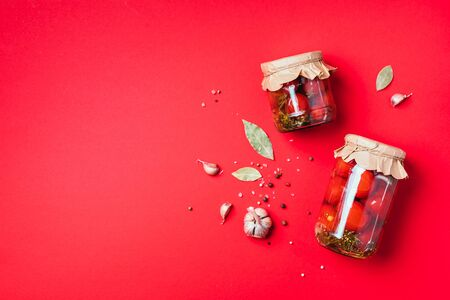 Pickled tomatoes in jar on blue background. Top view. Flat lay. Copy space. Canned and preserved vegetables. Ingredients for vegetables preserving. Healthy fermented food concept