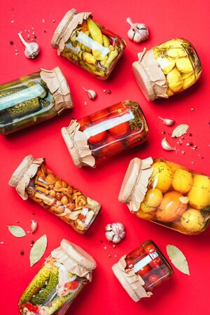 Canned and preserved vegetables in glass jars over red background. Top view. Flat lay. Copy space