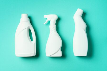 Composition with plastic bottles of cleaning products over blue background. Top view. Flat lay. Copy space. Plastic waste. Detergent bottle pattern.