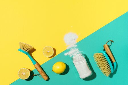 Baking soda, lemon, mustard powder and bamboo brushes against household chemicals products over yellow background. Top view. Copy space. Flat lay. Effective and safe house cleaning. Stock Photo