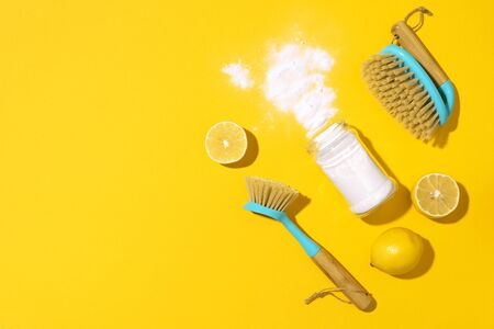 Baking soda, lemon, mustard powder and bamboo brushes against household chemicals products over yellow background. Top view. Copy space. Flat lay. Effective and safe house cleaning. Stockfoto
