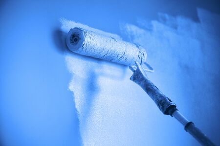 Painting wall with paint roller in monochrome color. Appartment renovation, repair, building and home concept. Trendy blue and calm color. Copy space, banner. Tools for painting walls