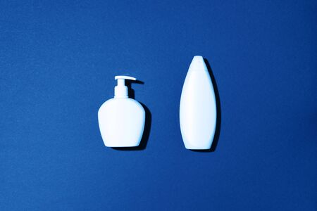 Shampoo and soap bottles on classic blue background. Top view. Flat lay. Copy space