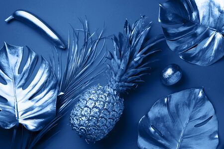 Painted exotic fruits, tropical palm, monstera leaves on classic blue background. Top view. Flat lay. Food concept. Creative layout of monochrome pineapple, banana, lemon with copy space Banco de Imagens