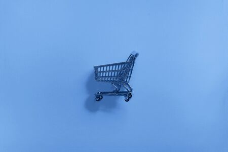 Shopping cart on classic blue background. Minimalism style. Shop trolley at supermarket. Trendy green and turquoise color. Sale, discount, shopaholism concept. Consumer society trend.