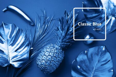 Painted exotic fruits, tropical palm, monstera leaves on classic blue background. Top view. Flat lay. Food concept. Creative layout of monochrome pineapple, banana, lemon with copy space Banco de Imagens - 135185920