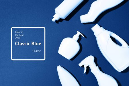 Cleaning products on classic blue background. Top view. Copy space. Chemical cleaning supplies. Stop plastic, recycling, separate collection of garbage concept.