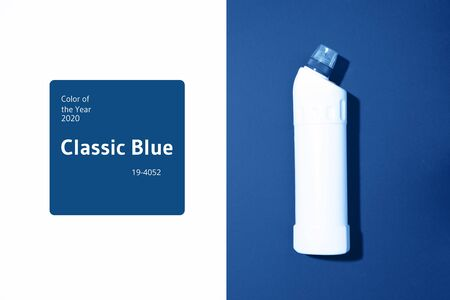 White plastic bottle of cleaning product, household chemicals or liquid laundry detergent on classic blue background. Top view. Flat lay. Copy space. Detergent bottle.
