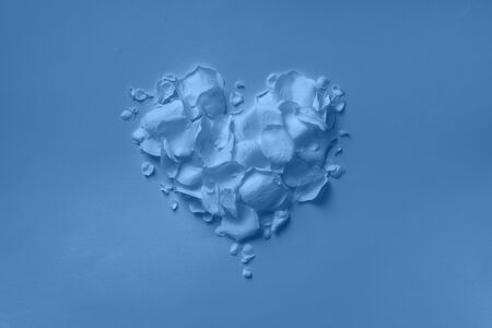 Heart shape made of rose petals on monochrome background. Top view, flat lay. Summer concept in trendy blue and calm color. Valentine's day. Creative layout Banco de Imagens - 135186757