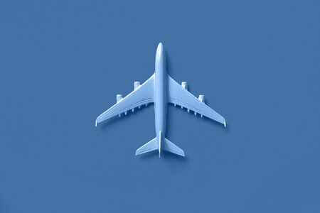 White plane, airplane in trendy blue and calm color. Rainbow gradient background with copy space. Top view, flat lay. Minimal style design. Travel, vacation concept 写真素材