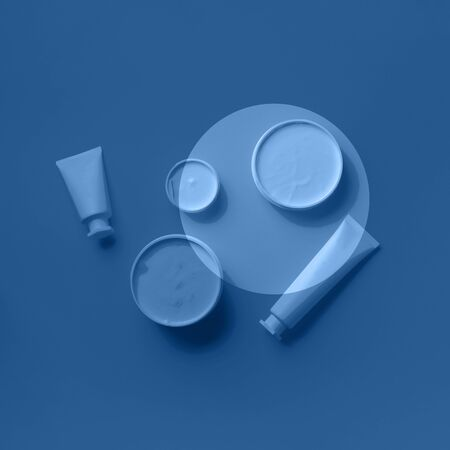 Cosmetics, skin care, beauty, body treatment concept. White cosmetic jar, tube, bottle and tropical monstera leaf over monochrome color background. Trendy blue and calm color 写真素材