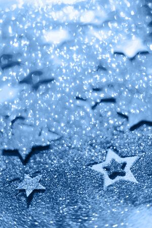 Christmas celebration. Abstract background for new year party. Patter of gold stars with lights, bokeh. Trendy blue and calm color. Glitter stars in monochrome color. Banco de Imagens - 135186765