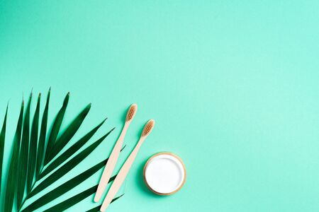 .Alternative health care concept. Natural toothpaste and wood toothbrush on trendy green background. Sustainable lifestyle. Zero waste.