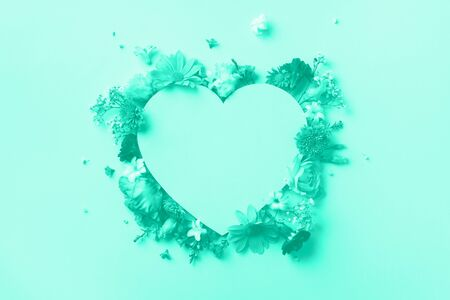 Creative layout with mint flowers, paper heart over mint color background. Top view, flat lay. Trendy green and turquoise color. Spring, summer or garden concept. Present for Woman day.