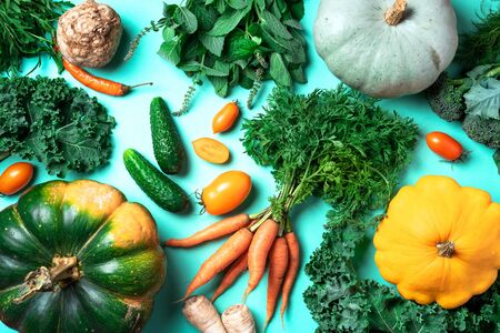 Autumn vegetables on trendy green background. Top view. Vegan and vegetarian diet, harvest concept. Ingredients for cooking - pumpkin, tomatoes, cucumber, pepper, kale, broccoli, celery.