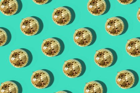 Creative Christmas pattern. Shiny gold disco balls over mint background. Flat lay, top view. New year baubles, star sparkles. Party time. Cristmas greeting card. Zdjęcie Seryjne