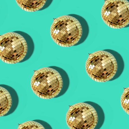 New year baubles. Shiny gold disco balls on mint background. Pop disco style attributes, retro concept. Creative Christmas pattern. Flat lay, top view Zdjęcie Seryjne