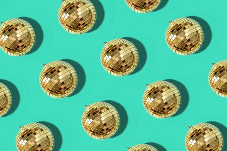 New year baubles. Shiny gold disco balls on mint background. Pop disco style attributes, retro concept. Creative Christmas pattern. Flat lay, top view.