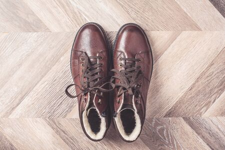 Top view of winter warm fashion male shoes on wooden background. Sale and shopping concept. Copy space Stock Photo