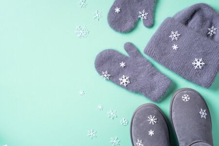 Winter warm clothes flat lay. Wool feminine clothes sweater, scarf, boots, snowflakes on blue background. Top view, copy space Banco de Imagens