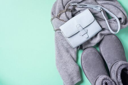 Fashion concept flat lay. Winter warm clothes flat lay on blue background. Wool feminine clothes sweater, scarf, boots, eco leather bag. Top view, copy space. Banner