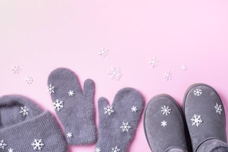 Winter warm clothes flat lay. Wool feminine clothes sweater, scarf, boots, snowflakes on pink background. Top view, copy space