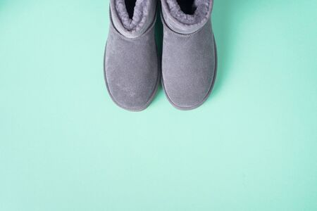 Grey ugg boots on blue background. Winter concept. Christmas and new year holiday. Copy space.