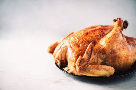 Whole roasted chicken in baking dish. Top view. Copy space. Macro shoot