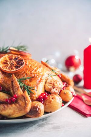 Whole roasted chicken with festive decoration, candles, light bokeh on concrete background. Copy space. Friends or family dinner. Festive Christmas table. Traditional Thanksgiving or Friendsgiving holiday celebration dish.