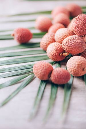 Lychee fruits with palm leaves on rattan background. Copy space. Exotic litchi, lichee fruits. Tropical food concept.