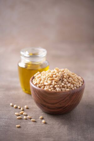 Shelled raw pine nuts in wooden bowl and pine nuts oil in bottle on wood textured background. Copy space. Superfood, vegan, vegetarian food concept. Macro of pine nuts texture, selective focus. Healthy diet Banco de Imagens