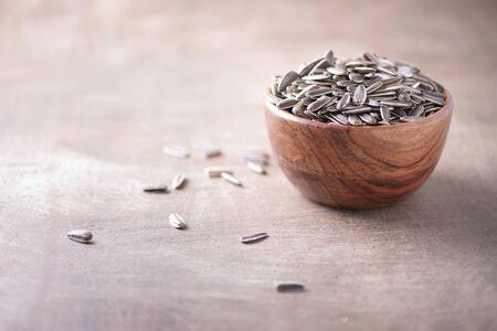 Sunflower seeds in wooden bowl on wood textured background. Copy space. Superfood, vegan, vegetarian food concept. Macro of sunflower seeds, selective focus. Healthy snack. Banco de Imagens