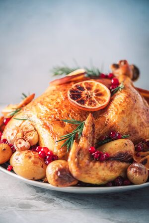 Roasted chicken with oranges, rosemary and cranberries on plate over concrete background. Traditional Thanksgiving or Friendsgiving holiday celebration dish. Friends or family dinner. Festive Christmas table.