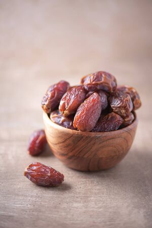 Dried date fruit in wooden bowl on wood textured background. Copy space. Superfood, vegan, vegetarian food concept. Macro of dates texture, selective focus. Healthy snack